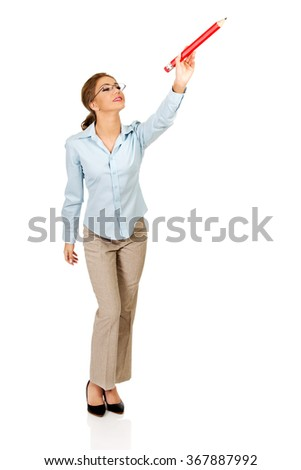 Businesswoman writing with big pencil. - stock photo