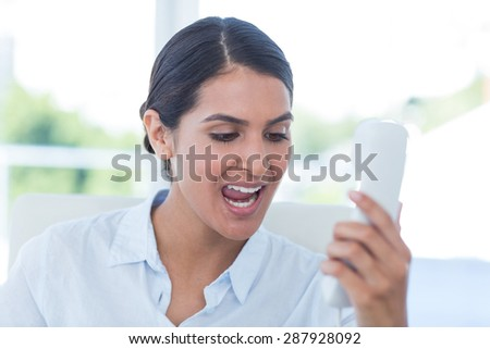 Businesswoman yelling at her phone in an office - stock photo