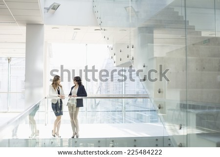 Businesswomen conversing against railing in office - stock photo