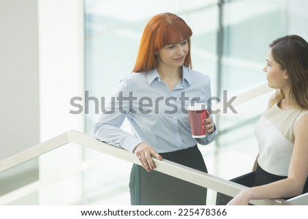 Businesswomen conversing while having coffee in office - stock photo