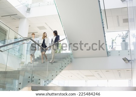 Businesswomen conversing while moving down steps in office - stock photo