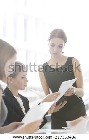 Businesswomen doing paperwork during coffee break - stock photo