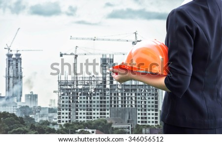 Businesswomen engineering standing in front of buildings and construction cranes - stock photo