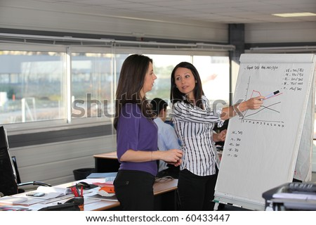 Businesswomen in front of a statistics board - stock photo