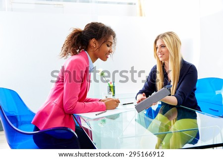 businesswomen interview meeting multi ethnic africand and blond sitting at office - stock photo