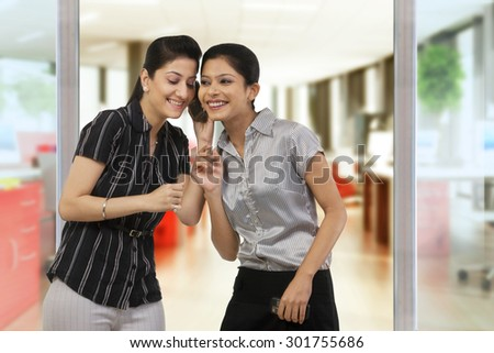 Businesswomen listening to a message on a mobile phone