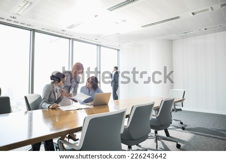 Businesswomen looking at documents in conference meeting - stock photo