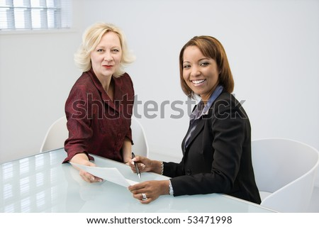 Businesswomen sitting at office desk discussing paperwork.