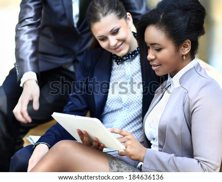 Businesswomen With Digital Tablet Sitting In Modern Office and discuss - stock photo