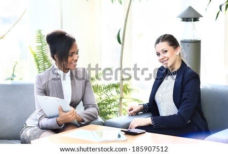 Businesswomen With Digital Tablet Sitting In Modern Office and discuss business matters - stock photo