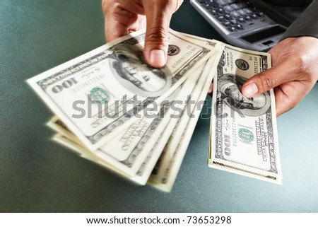 Busineswoman hand counting US dollar bills, taken close up