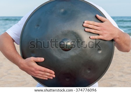 Busker on the sand beach and holding a handpan or hang with sea On Background. The Hang is traditional ethnic drum musical instrument - stock photo