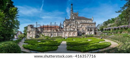 BUSSACO, PORTUGAL - 27 APRIL 2014: A panorama showing visitors enjoying the facade and gardens of the luxury hotel at Bussaco Palace near Luso in Portugal on a sunny summer's day.