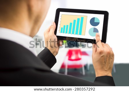 bussinesman looking at the stock market data on a tablet on the office.All screen content is designed by us and not copyrighted by others and created with wacom tablet and ps - stock photo