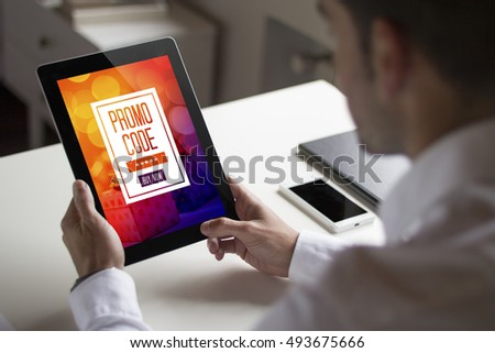 bussinessman at office holding a tablet exchanging a promotional code. All screen graphics are made up.