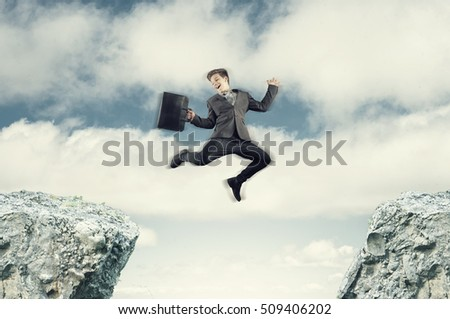 Bussinessman jumping from a rock cliff to another .