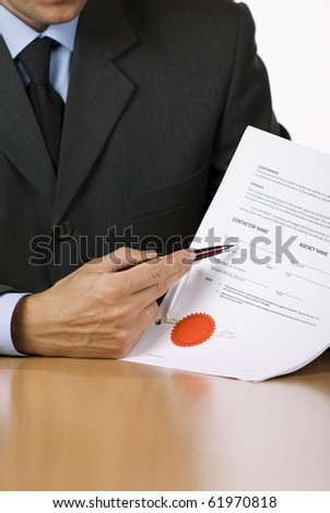 Bussinessman (or notary public) holding pen pointing at signature place on a contract document - stock photo
