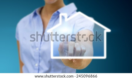 Bussinesswoman drawing a house with her finger on a tactile screen - stock photo