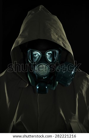 Bust of a man in chemical protection suit with a hood and a gas mask. Low key - stock photo