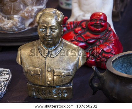 Bust of China's former Chairman Mao Zedong and red Laughing Buddha figurine at background. Still life at flea market in Paris (France). Idea of the contrasts in life. - stock photo