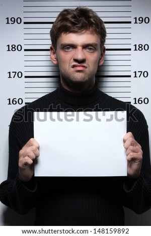 Busted burglar. Angry burglar holding a white poster while standing against police line-up - stock photo