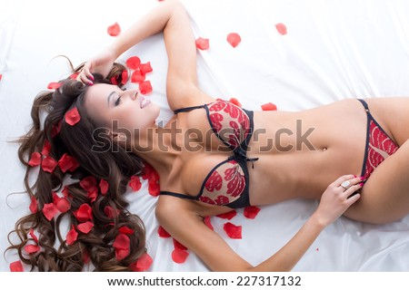 Busty lingerie model luxuriating on satin sheets - stock photo