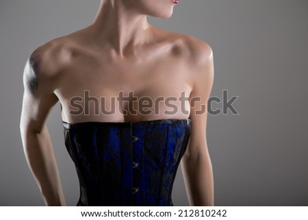 Busty young woman in black and blue corset, studio shot