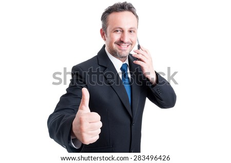 Busy and confident business man showing thumb up and talking on the phone - stock photo