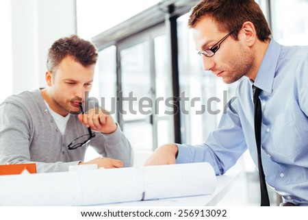 Busy architects trying to solve an architectural problem - stock photo