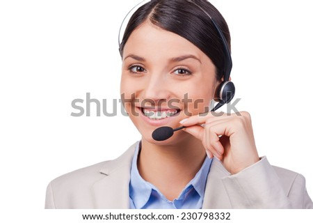 Busy at her work. Confident young customer service smiling while standing against white background  - stock photo