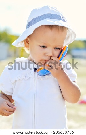 busy baby girl walking with toy phone - stock photo