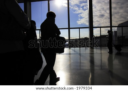 Busy business travelers in airport terminal - stock photo