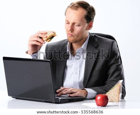 Busy businessman in office attire eating a sandwich at his desk, working through his lunch break hour - stock photo
