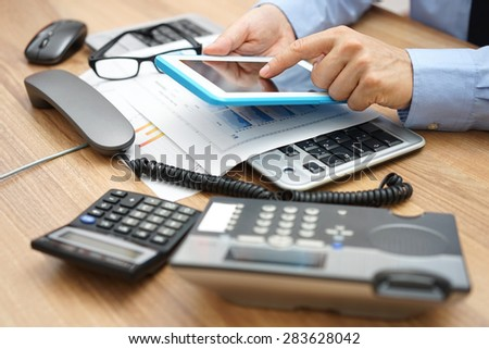busy businessman  in office with full of accessories on desk with telephone handset off the hook and working on tablet computer