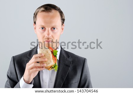 Busy businessman on the move, eating lunch a take away sandwich roll along the way - stock photo