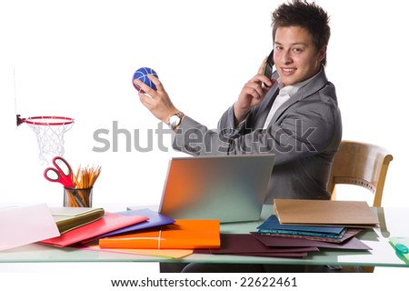 Busy businessman playing office basketball and talking on a phone