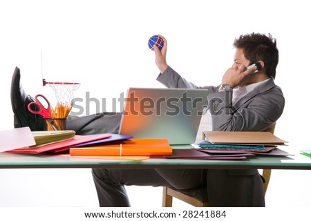 Busy businessman playing office basketball and talking on a phone - stock photo