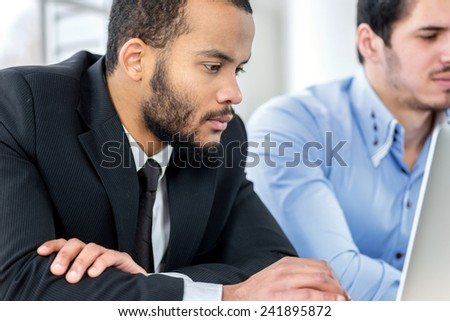 Busy businessman. Two confident businessman sitting at the negotiating table in the office while business people working at a laptop. Business people dressed in formal wear