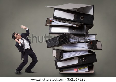 Busy businessman with a stack of files. - stock photo
