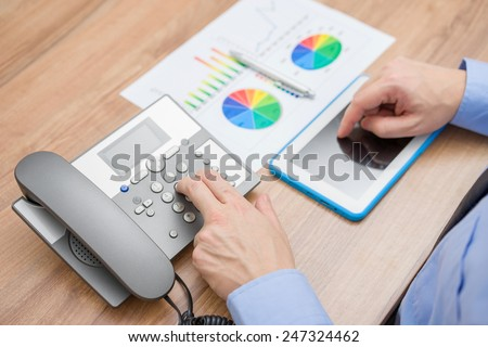 Busy businessman with report is pressing the number on the telephone keypad and working on tablet computer - stock photo