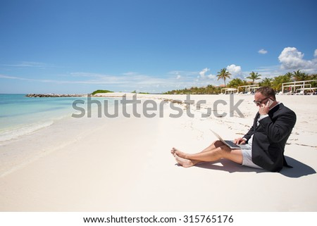 Busy businessman working on the beach - stock photo