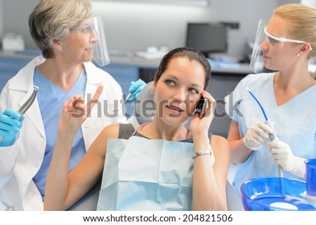 Busy businesswoman at dental surgery calling on phone dentists waiting - stock photo