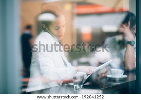 Busy businesswoman talking on phone and using tablet computer in coffee shop - stock photo