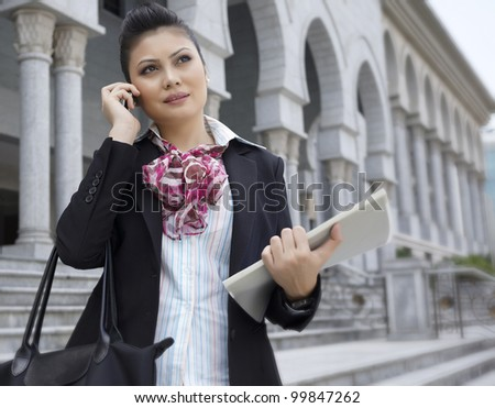 Busy Businesswoman using phone while holding files - stock photo