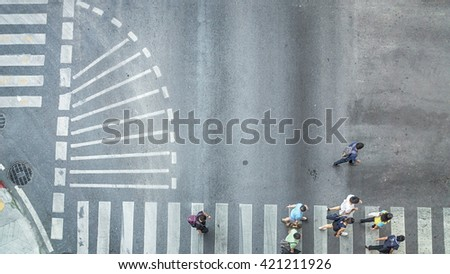 Busy city crowd move to pedestrian crossing on traffic road (Aerial photo, top view) - stock photo