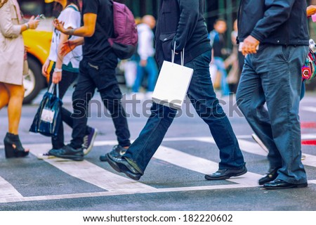 Busy city street people on zebra crossing with white paper bag. - stock photo