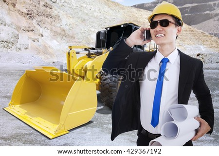 Busy contractor talking on the cellphone while carrying blueprints with backhoe on the background, shot at mining site