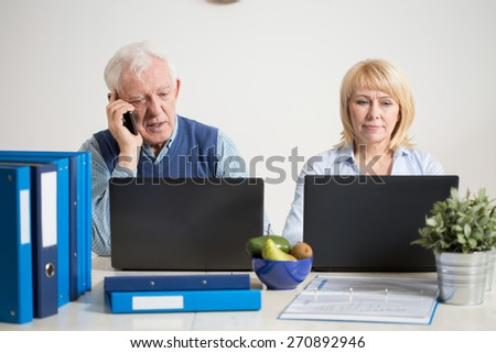 Busy couple using laptops to work at home office - stock photo