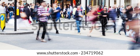 busy crowd of people in motion blur crossing a city street - stock photo