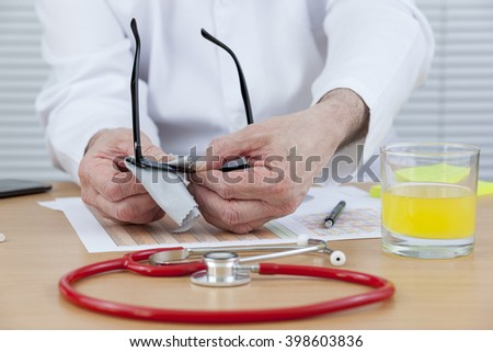 Busy doctor sitting at his desk cleaning his glasses with a red stethoscope laying in front of him